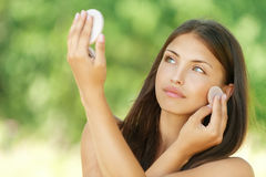 Young woman causes powder to skin. Beautiful young woman causes powder to skin, against summer green park Stock Images