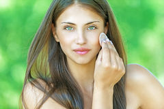 Young woman causes powder to skin. Beautiful young woman causes powder to skin, against summer green park Stock Photo
