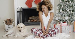 Young woman celebrating Christmas with her dog. Attractive trendy young African woman celebrating Christmas with her dog sitting in front of the decorated stock video