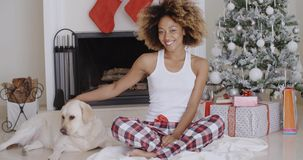 Young woman celebrating Christmas with her dog. Attractive trendy young African woman celebrating Christmas with her dog sitting in front of the decorated stock footage