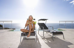 Young woman with celery on sun bed by infinity pool and sea, portrait, low angle view (lens flare) Stock Photo