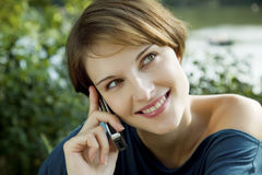 Young woman with a cell phone. Young woman talks outdoors with a cell phone in her hands Stock Photography