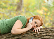 Young woman on cell phone. Young woman with red hair and green shirt laying on log or tree branch talking on cell phone, vegetation in background stock photos