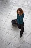 Young woman with cell phone and rolling luggage Royalty Free Stock Photos