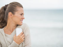 Young woman with cell phone standing on cold beach Royalty Free Stock Photo