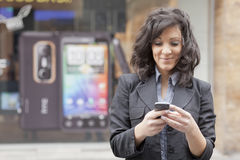 Young Woman with cell phone walking Stock Image