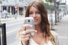 Young Woman with cell phone walking Royalty Free Stock Photography