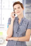 Young woman with cellphone. Young woman standing with cellphone, listening to phone call, smiling Royalty Free Stock Images