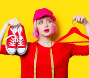 Young woman with centimeter, gumshoes and hanger Stock Images