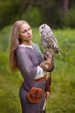 Young woman in chain mail looks an owl royalty free stock photography