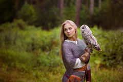 Young woman in chain mail with owl looking away royalty free stock photography