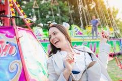 Young woman on chain swing ride, amusement park. Young woman having fun at fun fair, chain swing ride, amusement park Stock Image
