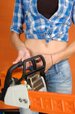 The young woman with a chainsaw Stock Images