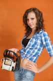 The young woman with a chainsaw. On a orange background stock photography