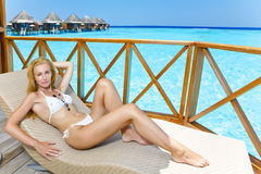 Young woman on chaise lounge Royalty Free Stock Image