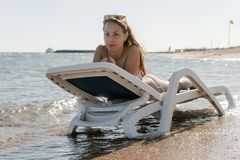 Young woman in chaise lounge at the sea beach. Girl relax on beach royalty free stock photos
