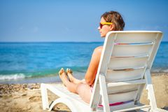 Young woman in chaise lounge at the sea beach. Girl relax on beach. royalty free stock image