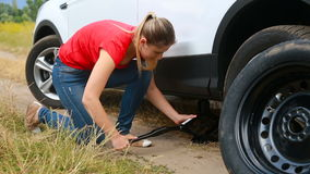 Young woman changing flat tire on car broken at field. Woman changing flat tire on car broken at field stock video footage