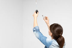 Young woman changing light bulb Royalty Free Stock Image