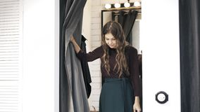 Young woman in a changing room. Young woman is standing in a changing room in a shop. She is pulling the curtain to demonstrate her choice, smiling and pulling stock video footage