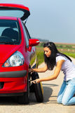 Young Woman Changing Tire. By the side of a rural road. Vertical Royalty Free Stock Photos
