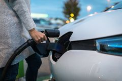 Young woman charging an electric vehicle royalty free stock image