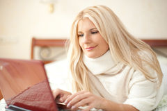 Young woman chating online with laptop on her bed Royalty Free Stock Photography