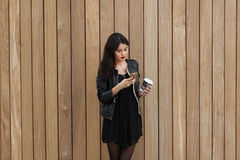 Young woman chatting on her cell telephone while standing against wooden wall background with copy space area, Royalty Free Stock Photo