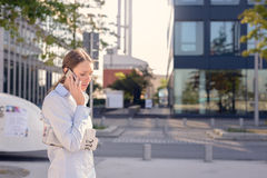 Young woman chatting on her mobile phone. Young woman with a folded newspaper under her arm standing chatting on her mobile phone in an urban street listening to Royalty Free Stock Image