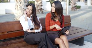 Young woman chatting on a mobile. Phone while sitting outdoors in the sun on a park bench with a stylish female friend or businesswoman stock video