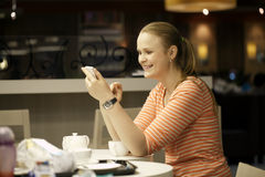 Young woman chatting on smartphone in cafe. Stock Images