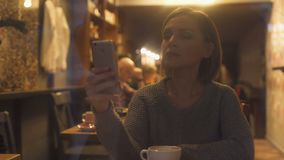 Young woman chatting on smartphone, sitting in cozy coffee house, free wi-fi. Stock footage stock footage