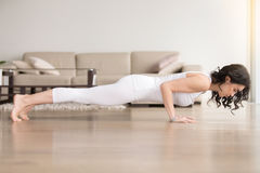 Young woman in chaturanga dandasana pose, hotel cozy living room Stock Photo