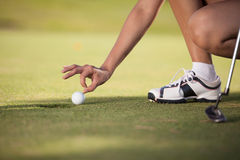 Young woman cheating at golf Stock Images