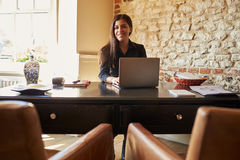 Young woman at the check-in desk of a hotel looks to camera royalty free stock photos