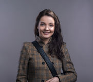 Young woman in checked brown winter coat. Studio shot. Royalty Free Stock Photography