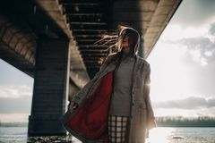 Young woman walks on river bank under bridge at sunset. royalty free stock photography