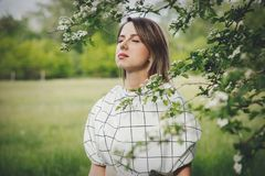 Young woman in a checkered dressstay near a flowering tree royalty free stock photo