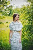 Young woman in a checkered dressstay near a flowering tree royalty free stock images