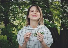 Young woman in a checkered dressstay near a flowering tree stock photo