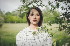 Young woman in a checkered dressstay near a flowering tree royalty free stock photography