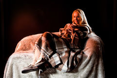 Young Woman With The Checkered Plaid. Young blonde woman lying on sofa with checkered plaid Royalty Free Stock Photo