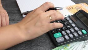 Young woman checking bills, taxes, bank account balance and calculating expenses. Close up of female accountant making calculation