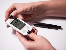 Young woman checking blood sugar level Royalty Free Stock Photos