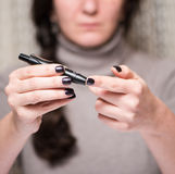 Young woman checking blood sugar level Royalty Free Stock Images