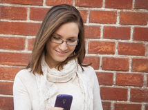 Young woman checking cell phone street Stock Photos