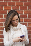 Young woman checking cell phone street Royalty Free Stock Image