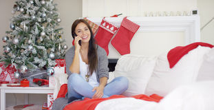 Young woman checking for Christmas messages. Attractive young woman checking for Christmas messages on her mobile phone with a happy smile as she relaxes at home Stock Images