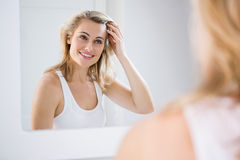 Young woman checking her hair in bathroom mirror Royalty Free Stock Image