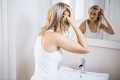 Young woman checking her hair in bathroom mirror Royalty Free Stock Images